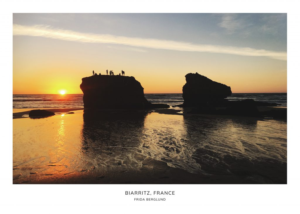 People on a rock in the sunset in Biarritz France